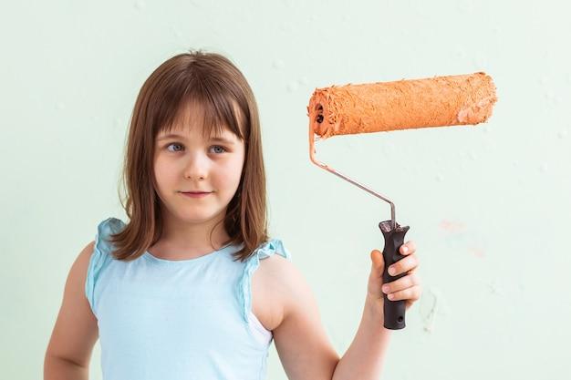 Gelukkig kind meisje schildert de muur met oranje verf,