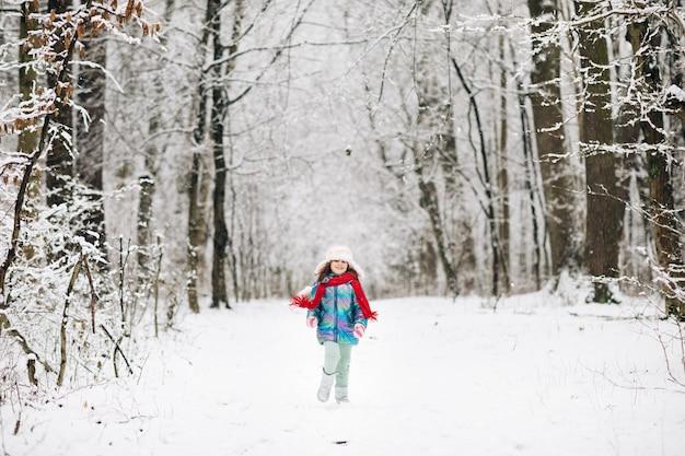 Gelukkig kind meisje speelt met een sneeuw in de winterdag. Premium Foto