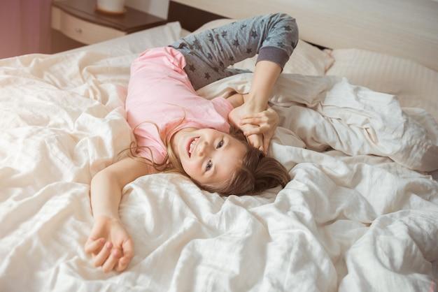 Gelukkig kind meisje strekt zich uit op het bed thuis terwijl coronavirus-epidemie. verveeld eenzaam kind. moeilijkheden van gezin met kinderen tijdens quarantaine. blijf thuis