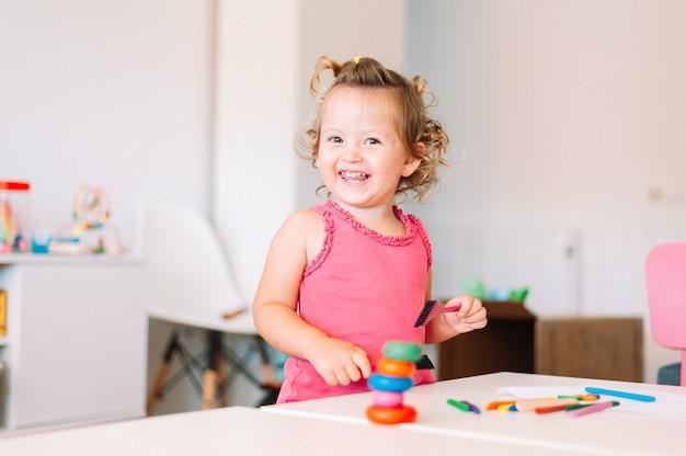 Gelukkig kind meisje tekent met kleurpotloden