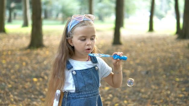 Gelukkig kind meisje zeepbellen blazen buiten in groen park. outdoor zomeractiviteiten concept.
