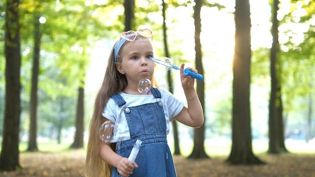 Gelukkig kind meisje zeepbellen blazen buiten in zomer park.