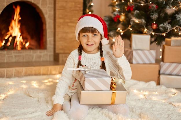 Gelukkig kind meisje zittend in de buurt van de kerstboom op kerstavond op de vloer en zwaaiende hand naar camera