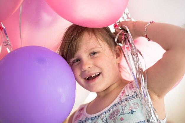 Gelukkig kind met ballonnen thuis, levensstijl