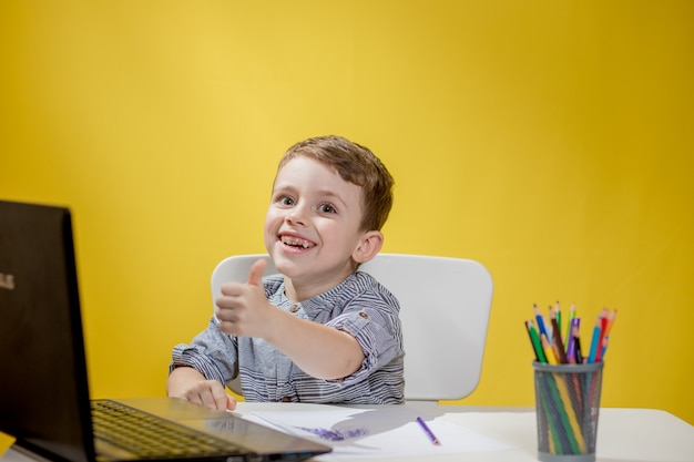 Gelukkig kind met behulp van digitale laptop huiswerk op gele achtergrond.