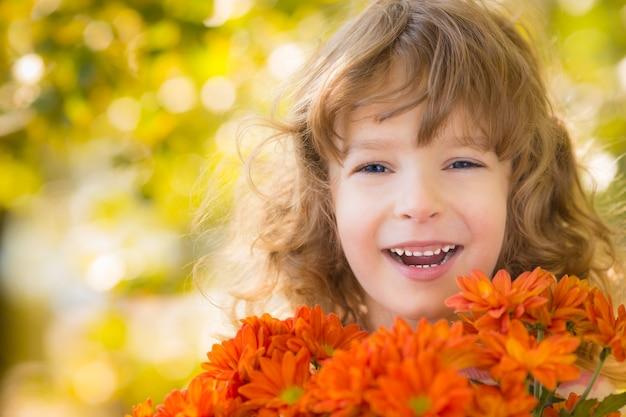 Gelukkig kind met bloemen buiten in herfstpark