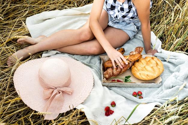 Gelukkig kind met brood in het gele veld van de de herfsttarwe. een veld met volwassen oren. een meisje zit op een sprei, vers fruit en bessen, brood en broodjes in een mand. buitenshuis village picnic.