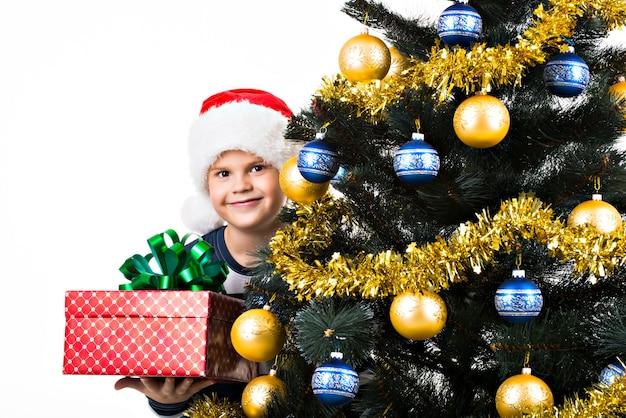 Gelukkig kind met cadeau in de buurt van de kerstboom