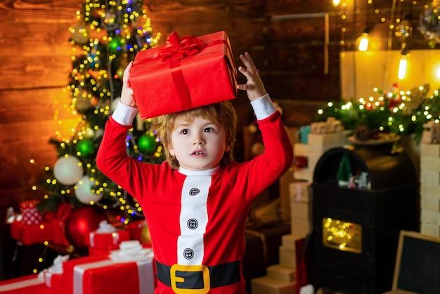 Gelukkig kind met de doos van de gift van kerstmis. blonde jongen die een rode doos boven zijn hoofd houdt. geïnteresseerd en verbaasd gezicht.