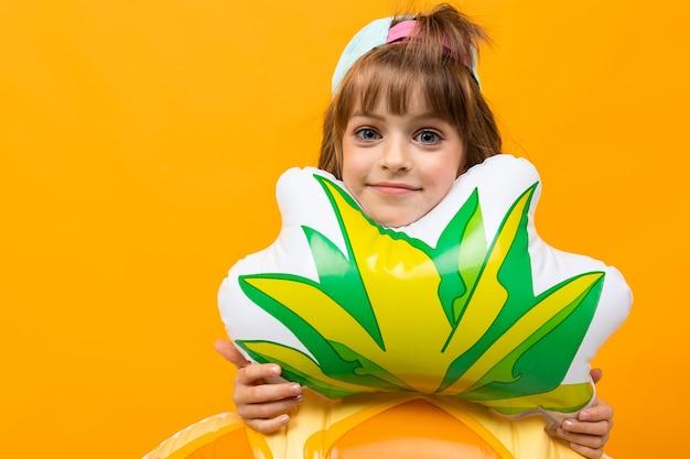 Gelukkig kind met een baseballpet in een zwembroek met een ananas rubberen ring op een oranje achtergrond.