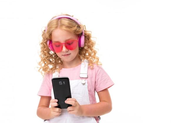 Gelukkig kind met eerlijk rood krullend haar chatten met vrienden en luisteren naar muziek