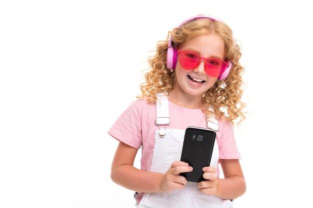 Gelukkig kind met eerlijk rood krullend haar chatten met vrienden, luister naar muziek en glimlacht