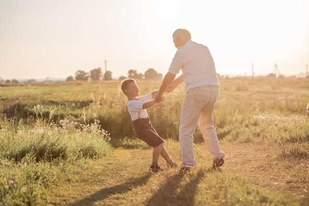 Gelukkig kind met grootvader spelen op de weide