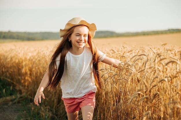 Gelukkig kind met hoed op zijn hoofd brengt zijn jeugd door op het platteland, rent vrolijk naast de tarwe...