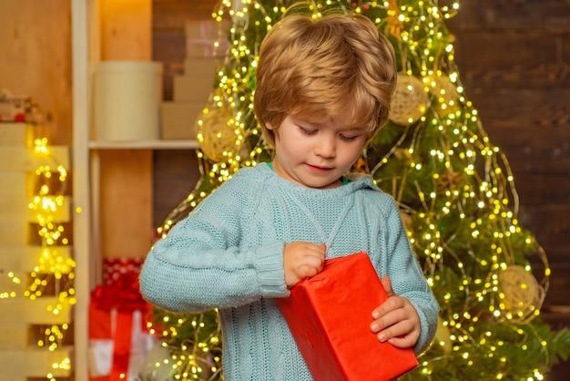 Gelukkig kind met kerstcadeau. nieuwjaars kinderen. nieuwjaar concept. kind met een kerstcadeau op