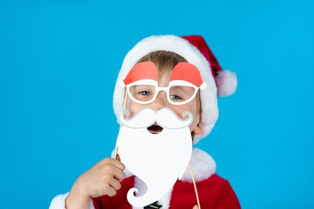 Gelukkig kind met kerstpapier rekwisieten tegen blauwe muur