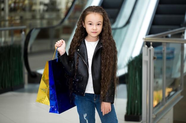 Gelukkig kind met kleurenpakketten op de roltrap in winkel van winkelcentrum