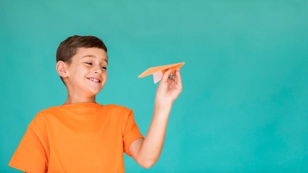 Gelukkig kind met papieren vliegtuigje met kopie ruimte