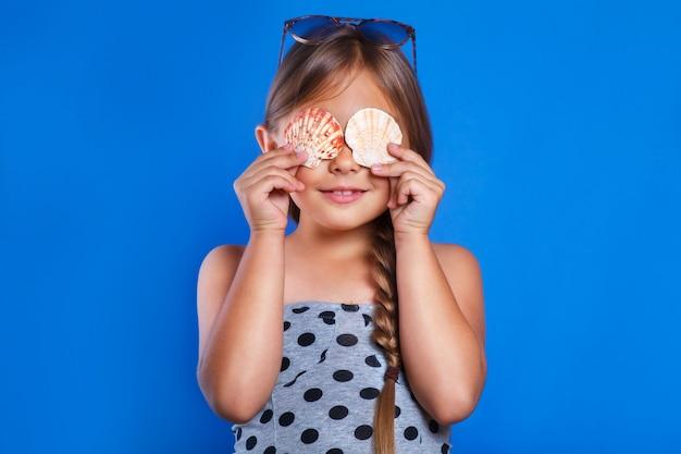 Gelukkig kind met schelpen. zomervakantie en reizen concept