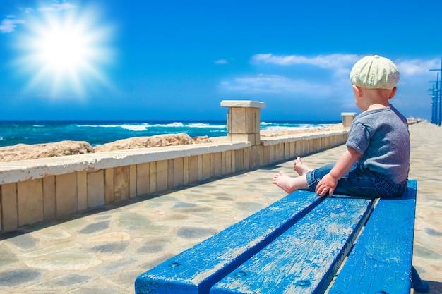 Gelukkig kind op het bankje aan zee in de open lucht