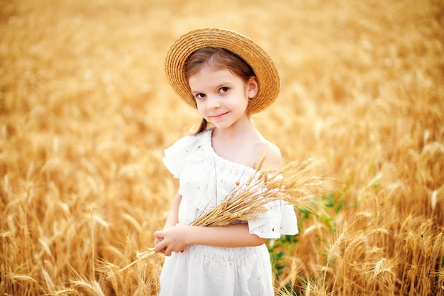 Gelukkig kind op het gebied van de de herfsttarwe. mooi meisje in witte jurk en strooien hoed veel plezier met spelen, oogsten