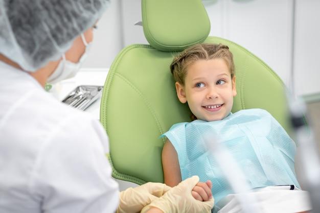 Gelukkig kind op regelmatige controle van tanden in tandheelkundige kliniek