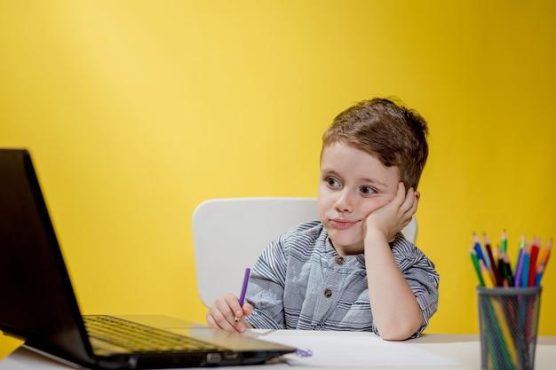 Gelukkig kind plezier kijken cartoon op laptop, kind met behulp van digitale pad zoeken naar de ideeën op internet voor zijn tekenkunst huiswerk