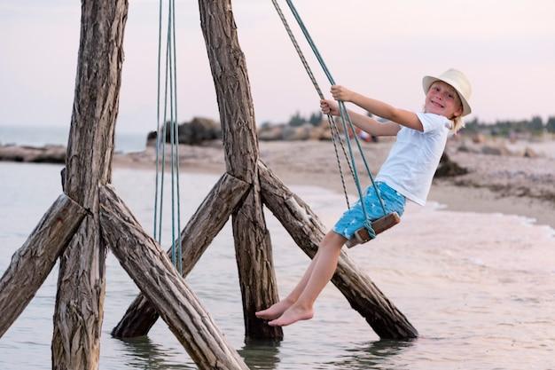 Gelukkig kind rijdt op touwschommel over water. zwaai langs de zee. vakantie met kinderen op zee.