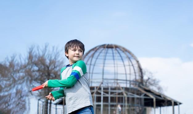 Gelukkig kind spelen in het park met een boemerang