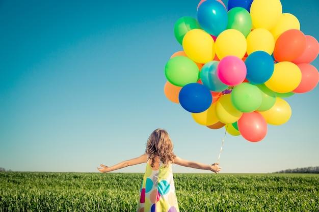 Gelukkig kind spelen met ballonnen buiten kind plezier in lente veld
