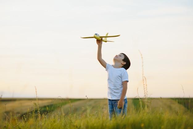 Gelukkig kind spelen met een vliegtuig speelgoed in de natuur tijdens de zomer zonsondergang