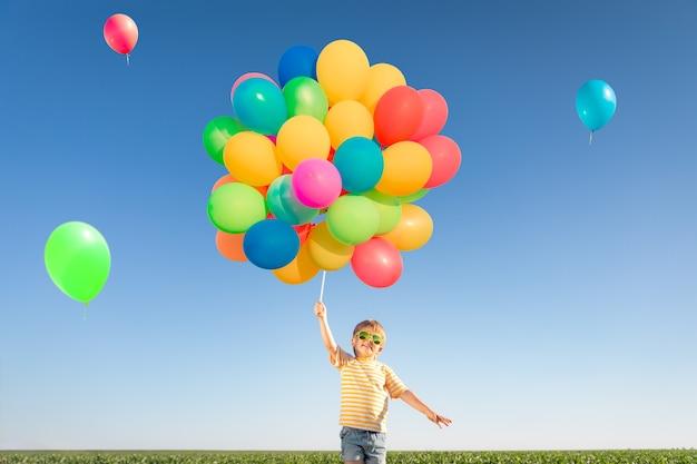 Gelukkig kind spelen met heldere veelkleurige ballonnen buiten. kind met plezier in groene lente veld tegen blauwe hemel. gezond en actief levensstijlconcept