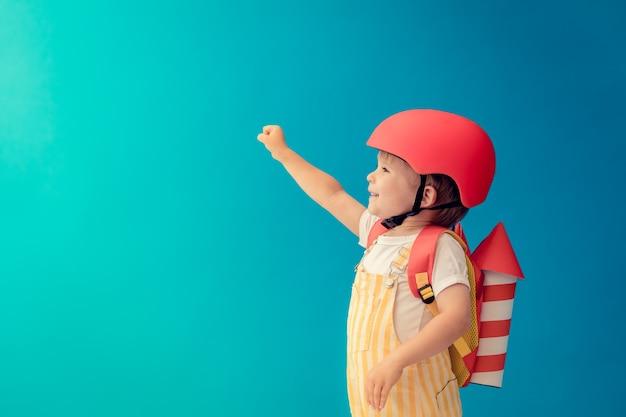 Gelukkig kind spelen met speelgoed papier raket tegen blauwe muur.