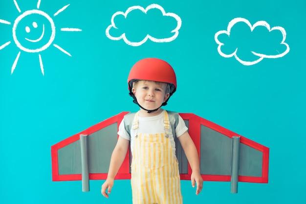 Gelukkig kind spelen met speelgoed papier vleugels tegen blauwe muur thuis.