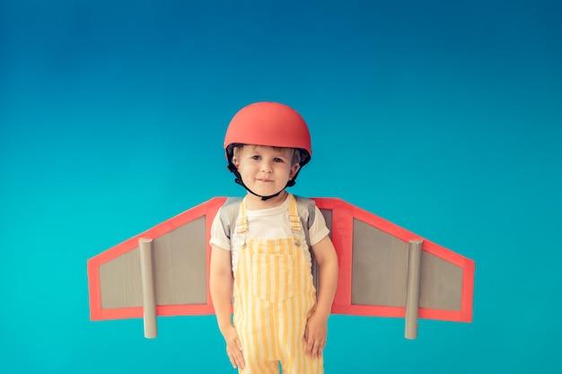 Gelukkig kind spelen met speelgoed papier vleugels tegen blauwe muur.