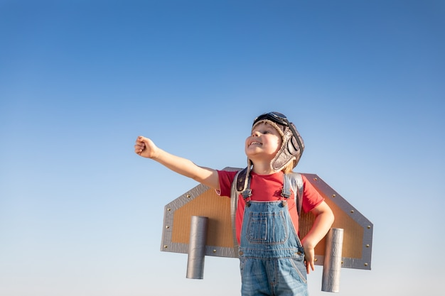 Gelukkig kind spelen met speelgoed vleugels tegen blauwe hemelachtergrond