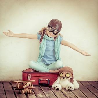 Gelukkig kind spelen met speelgoed vliegtuig thuis. retro getint