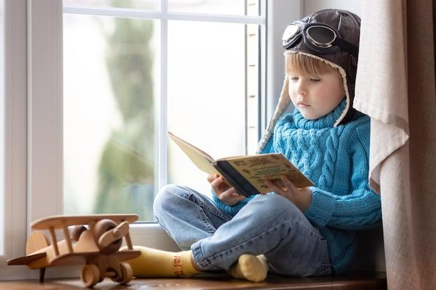 Gelukkig kind spelen met vintage houten vliegtuig binnen. kind leesboek thuis. blijf thuis en sluit af tijdens coronavirus covid-19 pandemie concept concept