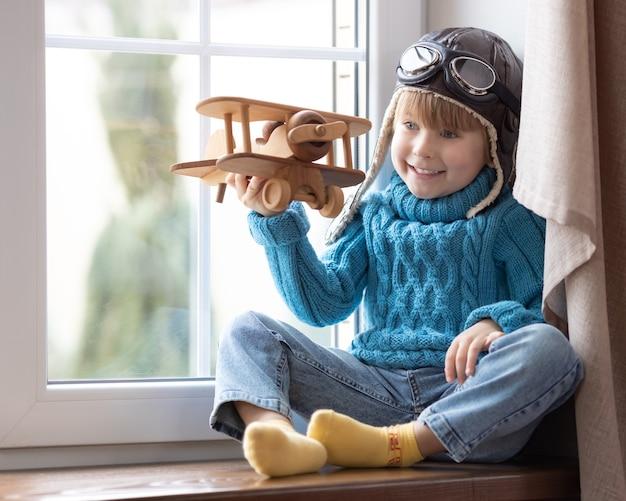 Gelukkig kind spelen met vintage houten vliegtuig binnen.