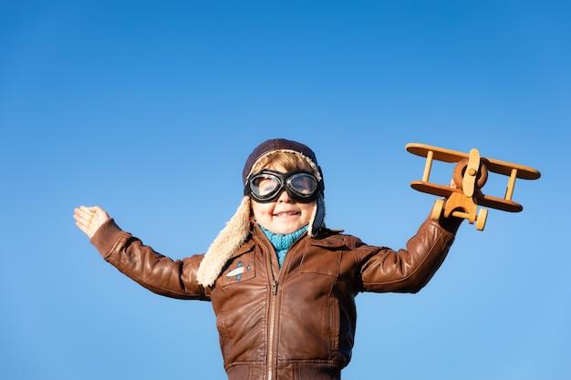 Gelukkig kind spelen met vintage houten vliegtuig tegen blauwe hemel.