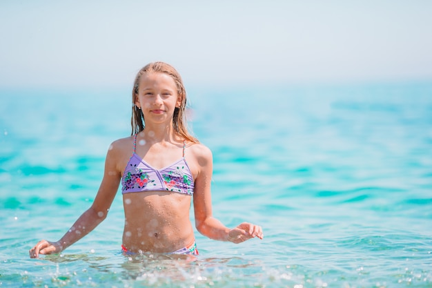 Gelukkig kind spetteren in de golven tijdens zomervakantie
