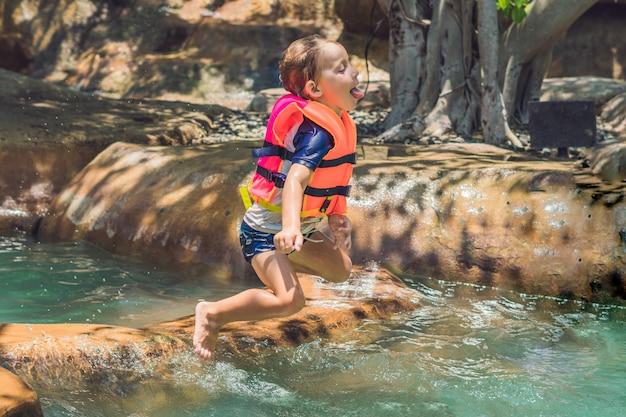 Gelukkig kind springt in de vijver en verhoogt op een zonnige dag veel spray
