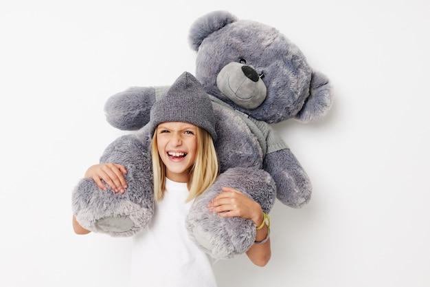 Gelukkig kind teddybeer in de handen van plezier op een lichte achtergrond