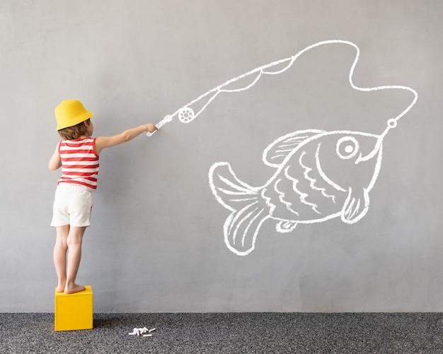 Gelukkig kind tekent een krijtvis op de muur kinderen verbeelding en zomervakantie concept