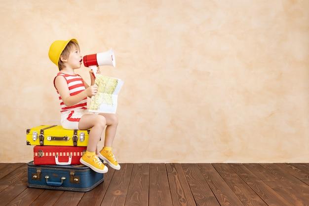 Gelukkig kind thuis spelen. glimlachend kind droomt van zomervakantie en reizen. verbeelding en vrijheid concept