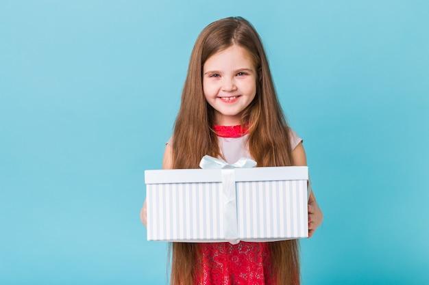 Gelukkig kind verjaardagscadeautjes houden op een blauwe muur.