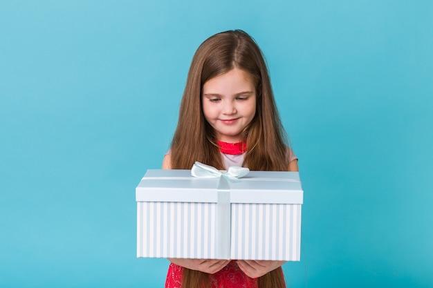 Gelukkig kind verjaardagscadeautjes houden op een blauwe muur