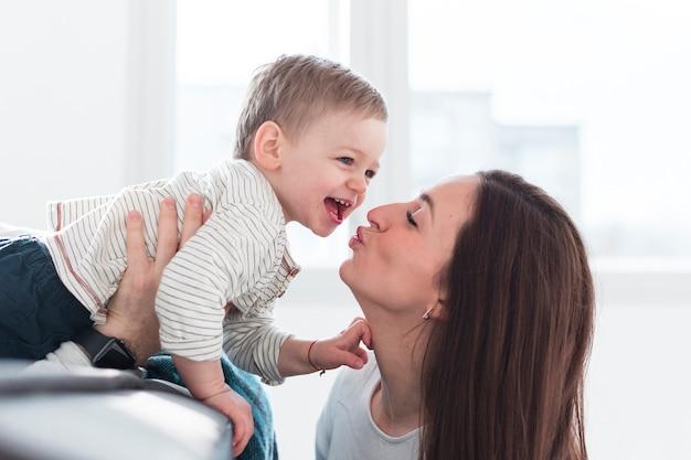 Gelukkig kind wordt gekust door moeder