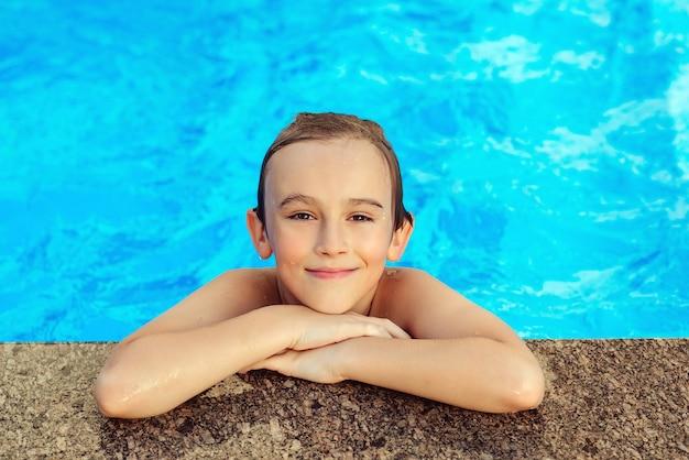 Gelukkig kind zwemmen in het buitenzwembad. zomer vakantie concept. waterspelletjes en waterpret voor kinderen.