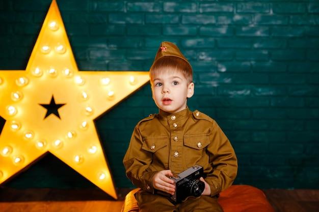 Gelukkig kindfotograaf met filmcamera. schattige jongen neemt foto met vintage camera. kind fotograferen in professionele fotostudio.